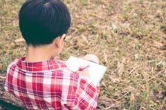 Rückseitige Ansicht Jungenschreiben auf Notizbuch getrennte alte Bücher Weinlese s Lizenzfreie Stockbilder