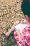 Rückseitige Ansicht Jungenschreiben auf Notizbuch getrennte alte Bücher Weinlese s Stockfoto