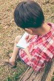 Rückseitige Ansicht Jungenschreiben auf Notizbuch getrennte alte Bücher Weinlese s Stockfotos