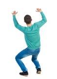 Rückseitige Ansicht Mann schützt Hände vor, was von oben fällt lizenzfreie stockbilder