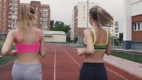 Rückseitige Ansicht Morgens streben zwei Mädchen herein Sport an und rütteln am Stadion stock footage