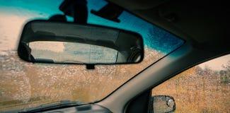Rückspiegel eines Autos auf einem Hintergrund des Glases in den Tropfen von a Stockfoto
