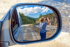 Rückspiegel Frau, die Fotos der Landschaft macht Lizenzfreie Stockbilder