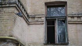 Rückstand in zerstörter Stadt während des Krieges, verlassenes Gebäude mit zerbrochener Fensterscheibe stock footage
