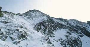 Rückwärtige Antenne über schneebedecktem Berg des Winters mit den Bergsteigenskifahrerleuten, die herauf das Klettern gehen Schne stock footage