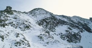 Rückwärtige Antenne über schneebedecktem Berg des Winters mit den Bergsteigenskifahrerleuten, die herauf das Klettern gehen Schne stock video footage