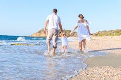 Rückwärtige glückliche dreiköpfige Familie - Mutter, Vater- und Tochterhändchenhalten und haben Spaß, die auf den Strand gehen Fa lizenzfreies stockfoto