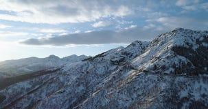 Rückwärtige von der Luftdraufsicht über weißen Schneeberg im Winter Forest Woods Snowy-Gebirgsstraßen-Weg establisher Sonnenunter stock video footage
