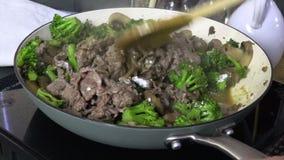 Rühren des Mehls in Rindfleisch und in Brokkoli in einer Wanne stock video