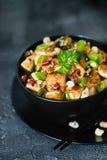 Rühren Sie gebratenen Tofu, Acajoubaum, Paprika auf dunklem Hintergrund Stockfotografie