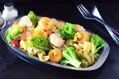 Rühren Sie gebratenes Hühnerleiste mit Gemüse und Teigwaren auf einem Metallbehälter auf einem schwarzen abstrakten Hintergrund Stockfoto