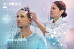 Rührende Drähte der aufmerksamen Krankenschwester bei der Prüfung sie vor der Herstellung des EEG stockbilder
