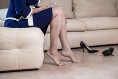 Rührende Füße der Geschäftsfrau mit der Hand Geerntete Ansicht von unten des Seitenansichtporträts Frau ` s von Beinen und von sc lizenzfreies stockbild