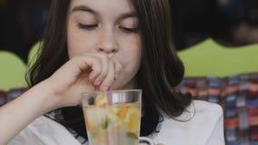 Rührende Limonade des schönen Mädchens mit Röhrchen und Lächeln an der Kamera stock video