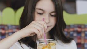 Rührende Limonade des schönen Mädchens mit Röhrchen und Lächeln an der Kamera stock footage