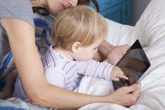 Rührende Tablette des Babys auf Bett Lizenzfreie Stockfotos