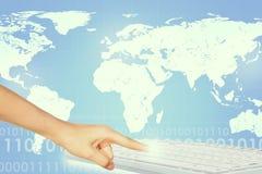 Rührende Tastatur des Menschenfingers auf Weltkarte Stockbild