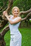 Rührender Baum der attraktiven Frau im Park Lizenzfreie Stockbilder