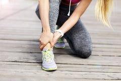 Rührender Fuß des Läufers des weiblichen Athleten in den Schmerz draußen Stockfoto
