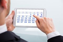 Rührender Kalendertag des Geschäftsmannes an der digitalen Tablette im Büro Lizenzfreies Stockbild