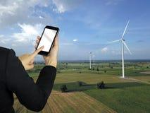 Rührender Telefonschirm der Geschäftsfrau an Windkraftanlagebauernhofpark g Stockfotografie