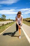 Rührendes Knie der athletischen Frau durch schmerzliche Verletzung herein Lizenzfreies Stockbild