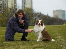 Rütteln der Hände mit Hund Stockfoto
