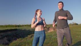 Rütteln Sie draußen, die glücklichen jungen athletischen Paare, die Stoß in der Natur genießen und in sonniges Tageslicht nach He stock footage