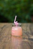 Rütteln Sie mit Cocktail der rosa Pampelmuse auf grünem Hintergrund bokeh Lizenzfreies Stockbild