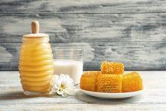 Rütteln Sie mit Honig, frischen Bienenwaben und Glas Milch Lizenzfreie Stockfotografie