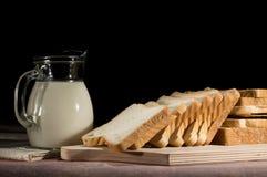 rütteln Sie mit Milch und Scheiben brot auf schwarzem Hintergrund Lizenzfreies Stockfoto