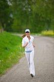Rütteln - sportive Frau, die auf Straße in der Natur läuft Stockfotografie