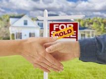 Rütteln von Händen vor neuem Haus und Verkaufszeichen Lizenzfreie Stockbilder