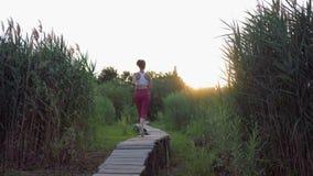 Rüttelndes Freien, aktive Sportfrau mit schönen Körperläufen auf Holzbrücke in der Natur unter Schilfen bei Sonnenuntergang stock footage