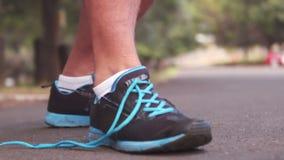 Rüttler, der seinen Schnürsenkel bindet stock video