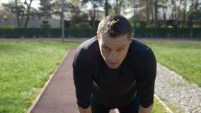 Rüttler des jungen Mannes, der für anziehenden Atem des Bruches auf athletischer Bahn im Freien stoppt stock footage