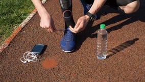 Rüttler mit dem smartwatch, das Spitzee bindet und Smartphone mit Kopfhörern und Wasserflasche auswählt stock video footage