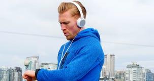 Rüttler mit Kopfhörern sein smartwatch beim Rütteln überprüfend, 4K 4k stock video footage