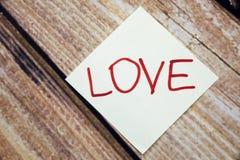 Ręcznie pisany papier z miłości pojęciem na drewnianym tle Retro tło z słowo miłością Walentynka dnia pojęcie z drewnianym Fotografia Royalty Free