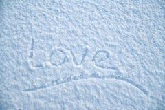 Ręcznie pisany podkreślający słowo «miłość «napisze na puszystym śniegu na mroźnym zima wieczór, to walentynki dni obraz royalty free