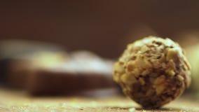 Ręcznie robiony czekoladowi cukierki spada na drewnianym tle, smakowici cukierki w zwolnionego tempa uhd zbiory