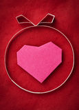 Ręcznie robiony papieru serce na czerwień papierze jako tło. Zdjęcie Stock