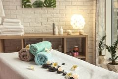 Ręczniki, świeczki i kamienie na masażu stole, fotografia royalty free