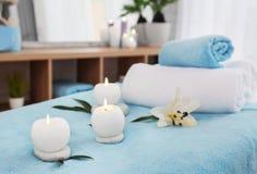 Ręczniki, świeczki i kamienie na masażu stole, fotografia stock