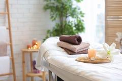 Ręczniki, świeczki i kwiat na masażu stole, zdjęcie stock