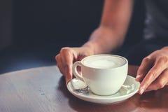 Ręk kobiety trzymają gorącego filiżanka kawy w sklepie z kawą obrazy stock
