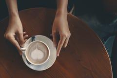 Ręk kobiety trzymają gorącego filiżanka kawy w sklepie z kawą obraz royalty free