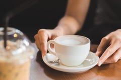 Ręk kobiety trzymają gorącego filiżanka kawy w sklepie z kawą zdjęcie stock