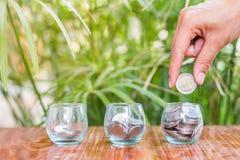 Ręka żeńskie kładzenie monety w słoju z pieniądze sterty kroka oszczędzania narastającym wzrostowym pieniądze Zdjęcie Stock