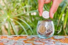 Ręka żeńskie kładzenie monety w słoju z pieniądze sterty kroka oszczędzania narastającym wzrostowym pieniądze Fotografia Stock